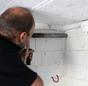 Handwerker bohrt Loch für Solarleitung.