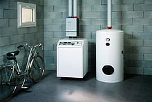 Auf dem Bild ist ein weißer Boiler im Keller zu sehen.