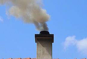 Rauchender Schornstein auf Hausdach