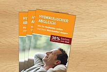 Flyer zum hydraulischen Abgleich gestapelt auf Holz-Oberfläche