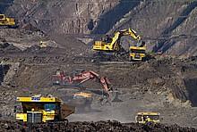 Gelbe Bagger graben in Kohle-Abbaugebiet. Rauch steigt von braunem Boden auf.