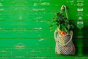 Grüne Holzwand, rechts ein Stoffbeutel mit Gemüse