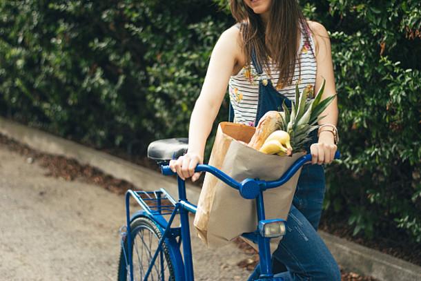 Frau mit einem Fahrrad und einer Papier-Einkaufstasche.