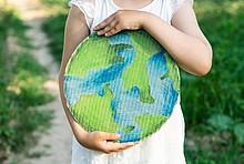 Kind hält Pappschild mit Weltkugel in den Händen