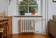 Ein Heizkörper unter dem Fenster im Wohnzimmer