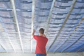 Handwerker installiert wasserführende Deckenheizung.