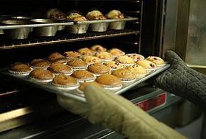 Hände mit Topfhandschuhen zieht Muffin-Blech aus dem Ofen.