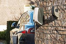 Tankstelle für ein Elektroauto an einer Hauswand, Elektroauto mit Ladekabel im Hintergrund