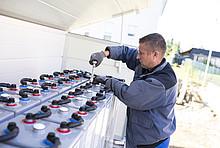 Handwerker mit Werkzeug an einer großen Metallkiste voller Bleispeicher
