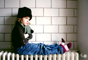 Kind sitzt auf einer Heizung