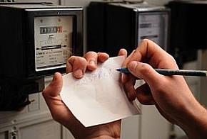 Hand mit Stift notiert Stromverbrauch auf Blatt Papier vor zwei Stromzählern
