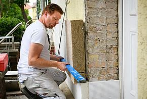 Sanieren & Klimaschutz: Ein Handwerker bringt eine Dämmung aus Hanf an der Fassade an.