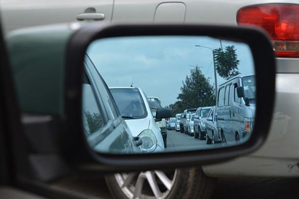 Im Seitenspiegel eines Autos ist ein Stau zu sehen.