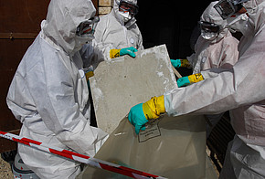 Personen in Schutzanzug packen verseuchtes Material in Tueten.