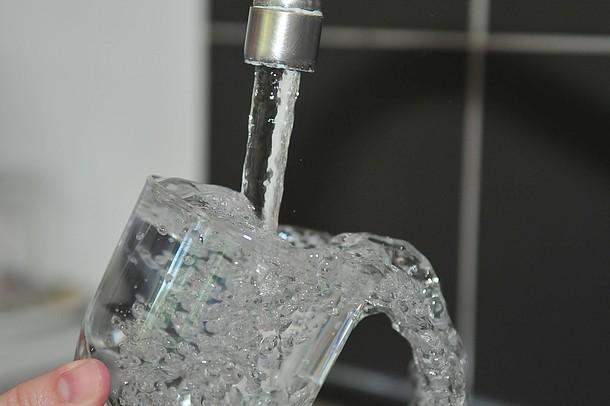 Ein Glas wird mit Leitungswasser gefüllt.
