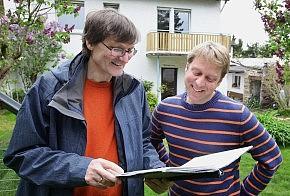 Energieberater mit Mappe und Eigentümer im Garten hinter dem Haus
