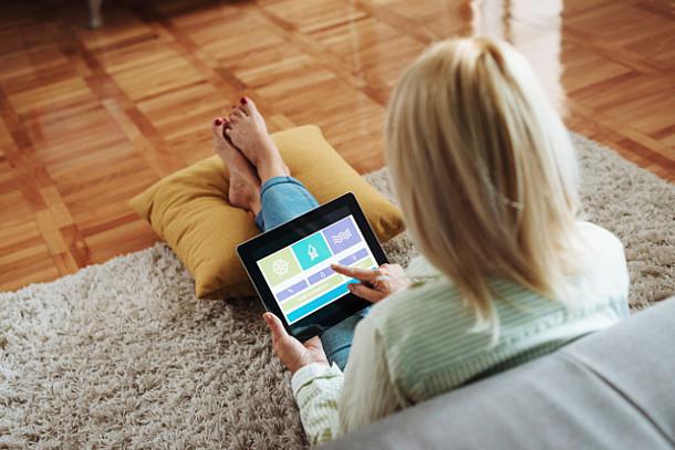 Frau überprüft am iPad die Energieeffizienz des Hauses.
