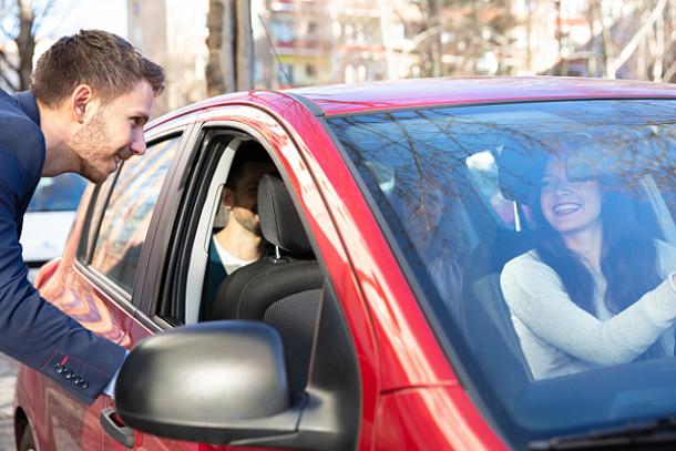 Auf dem Bild ist ein Mann zu sehen, der in ein volles Auto einsteigt.