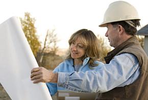 Mann mit Helm und Frau vor Plakat.