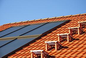 Fördermittel der KfW: Dach mit roten Dachziegeln und Solarzellen