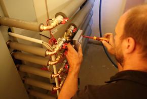 Handwerker installiert Wärmemengenzähler.