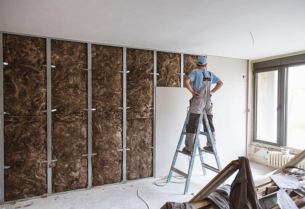 Mann dämmt eine Wand mit Unterkonstruktion.