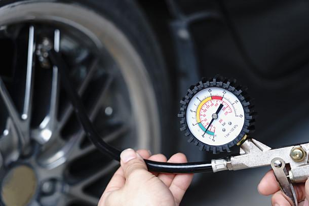 Auf dem Bild ist zu sehen, wie der Reifendruck von Autoreifen gemessen wird.