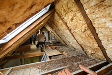 Handwerker bringen eine Dachdämmung an