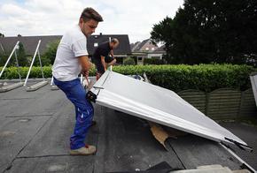 Handwerker tragen Kollektoren aufs Dach.