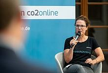 co2online-Geschäftsführerin Tanja Loitz mit Mikro auf dem Podium des Online-Klimatalks