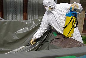Mann in Schutzanzug entsorgt Asbest