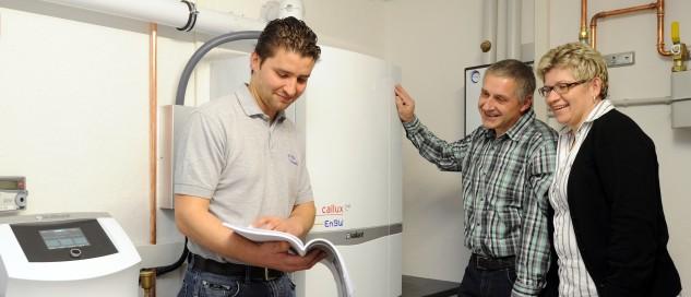 Ein Handwerker und zwei Kunden vor einer Brennstoffzellen-Heizung