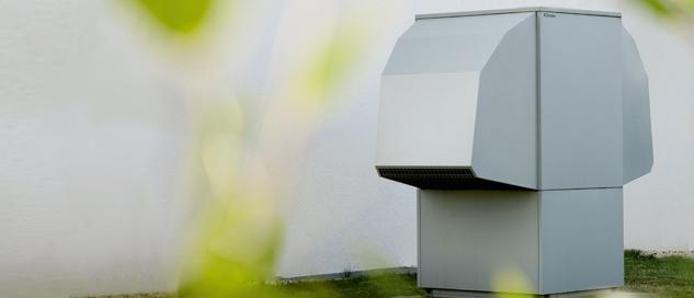 Eine Wärmepumpe im Garten: Sie versorgt die Heizkörper mit Wärme aus der Umwelt. Das Dossier erklärt, welche Bedingungen Ihr Haus erfüllen muss.